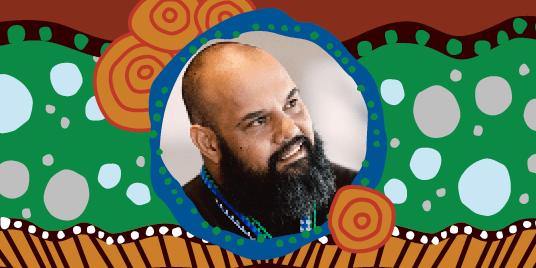man smiling with aboriginal artwork